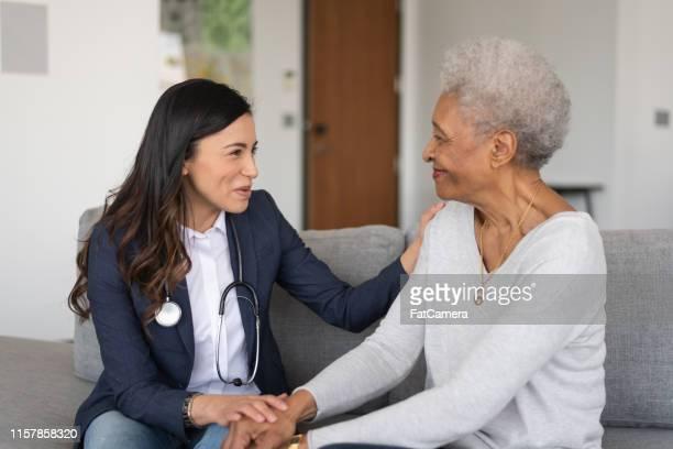 arzt im gespräch mit ihrem patienten - hausarzt stock-fotos und bilder