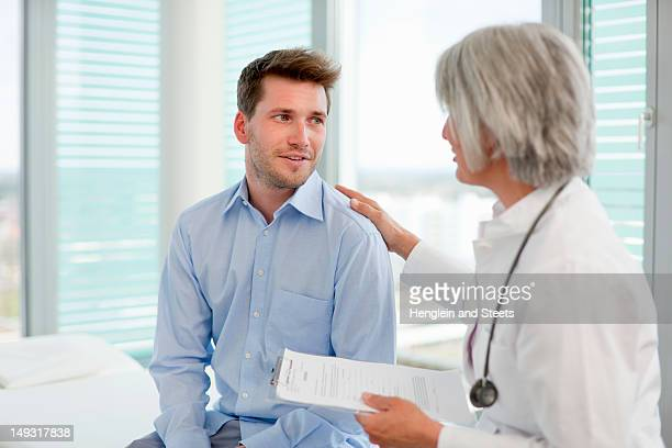 doctor talking to man in office - human body part stock pictures, royalty-free photos & images