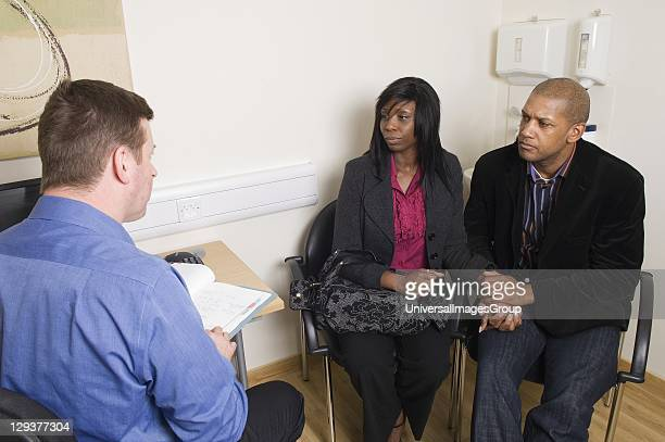 Doctor talking to mature couple holding hands Before treatment begins prospective patients have a consultation to discuss treatment and the...