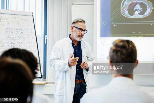 doctor talking to medical students - seminario riunione foto e immagini stock