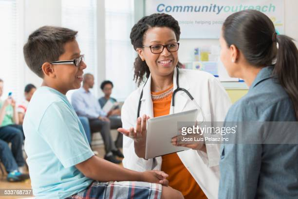 Doctor talking to mother and son in hospital
