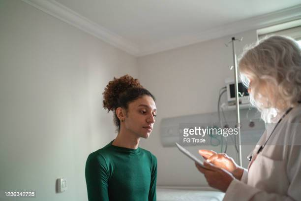 doctor talking to patient at hospital room with digital tablet - androgynous stock pictures, royalty-free photos & images