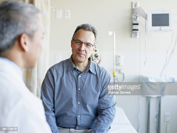 doctor talking to patient in hospital room - personnes masculines photos et images de collection