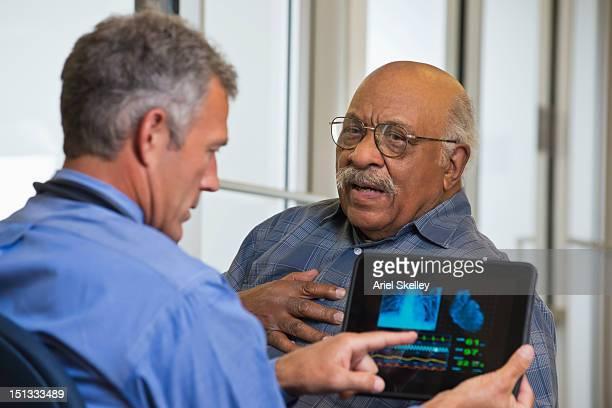 doctor talking to patient in hospital usando tableta digital - cardiólogo fotografías e imágenes de stock
