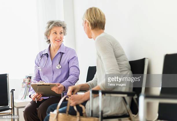 doctor talking to patient in waiting room, jersey city, new jersey, usa - outpatient care stockfoto's en -beelden