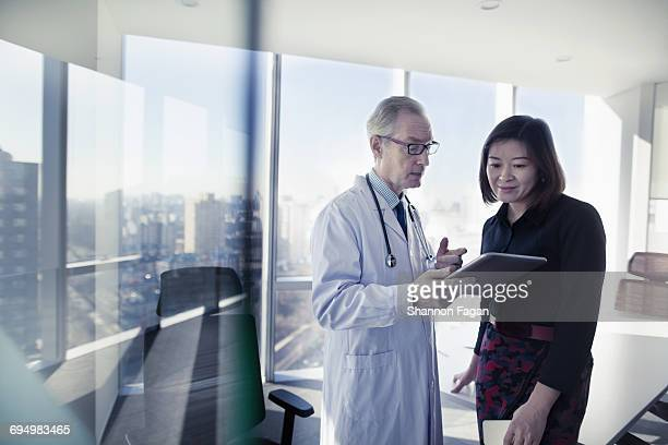 Doctor talking to patient using tablet in office