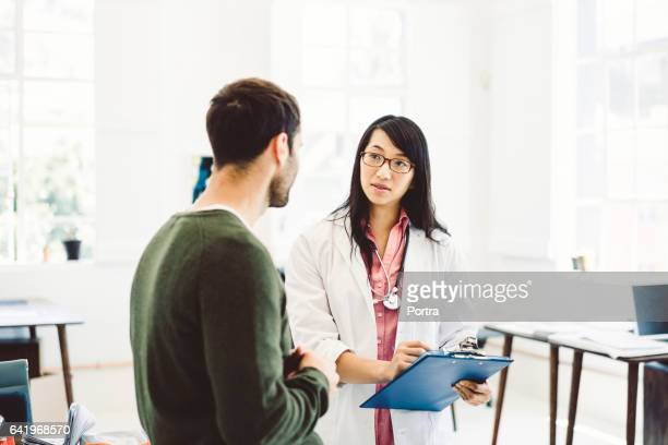 Doctor talking to patient while holding clipboard