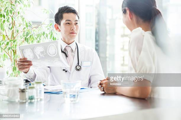 doctor talking to patient while looking at the x-ray photo - epilepsy stock pictures, royalty-free photos & images