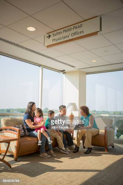 doctor talking to patients in waiting room - patients brothers stock pictures, royalty-free photos & images