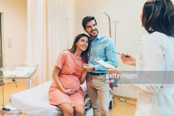 doctor talking to pregnant woman and her husband - cesariana imagens e fotografias de stock