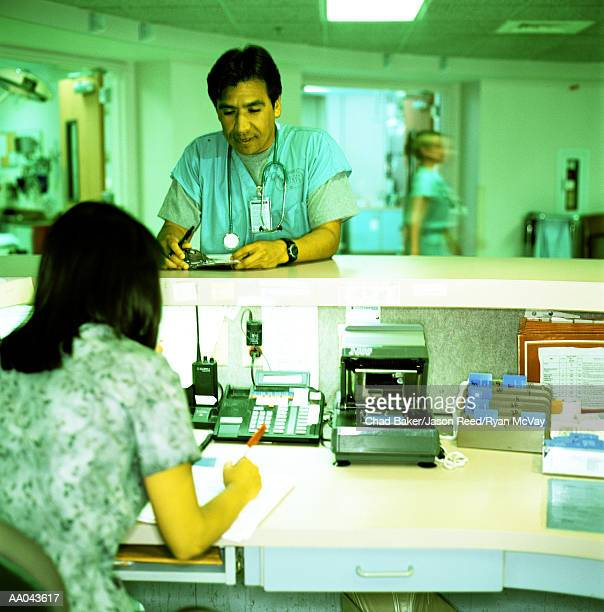 Doctor talking to receptionist in emergency room (cross-processed)