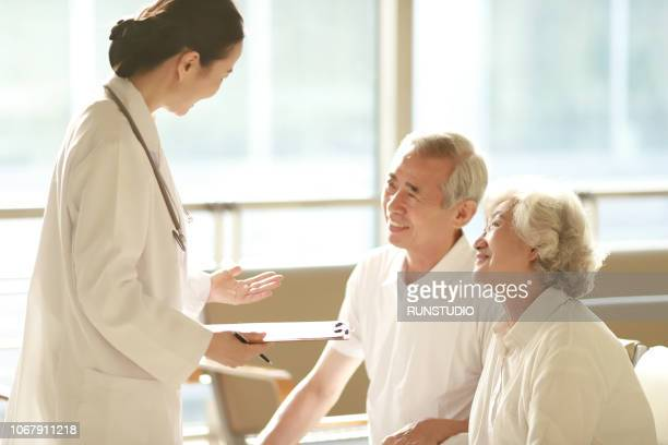 doctor talking to senior couple in hospital - 医療とヘルスケア ストックフォトと画像
