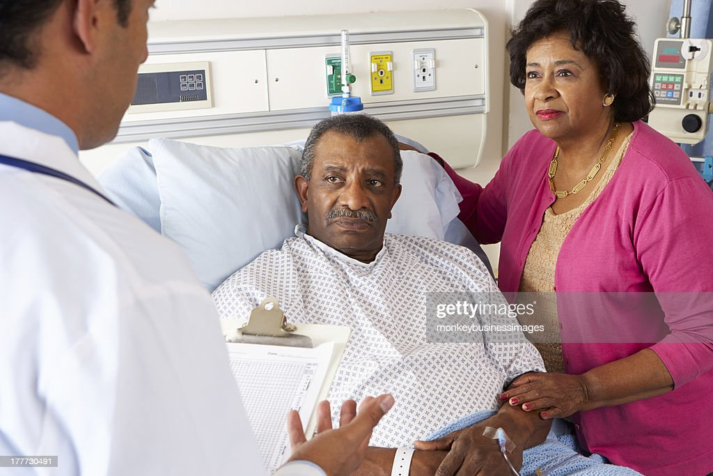 Doctor Talking To Senior Couple On Ward : Stock Photo