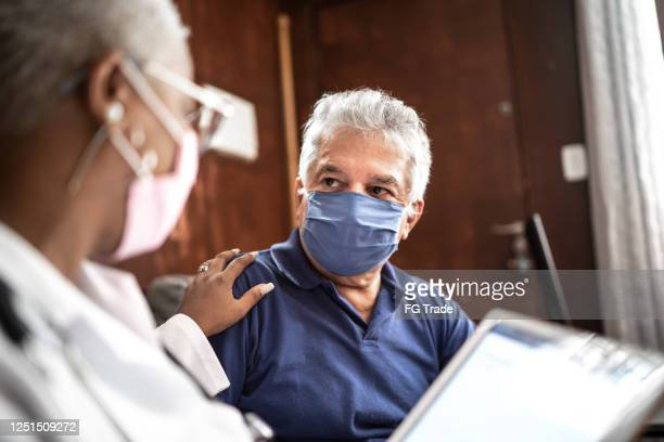 doctor talking to senior male patient in a home visit - respiratory disease stock pictures, royalty-free photos & images