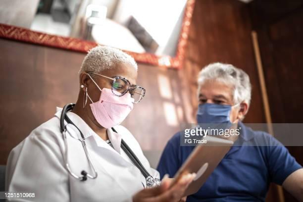 arts die aan hogere mannelijke patiënt in een huisbezoek spreekt - medicare stockfoto's en -beelden