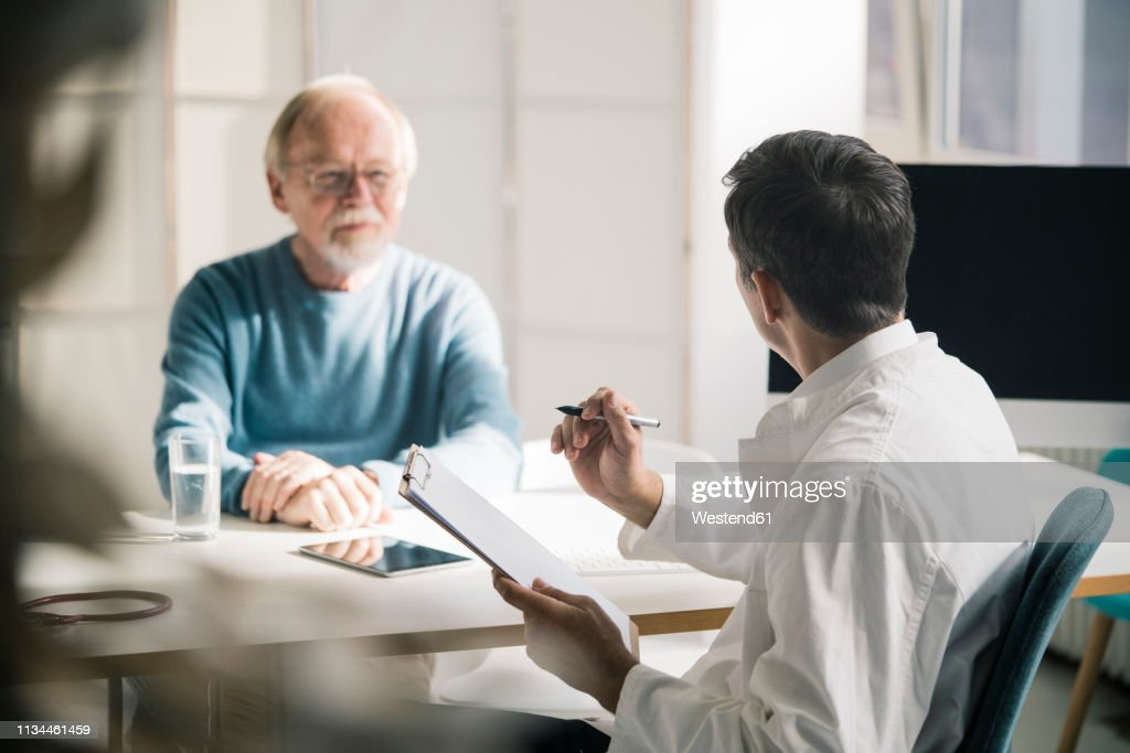 Doctor talking to senior patient in medical practice : Stock-Foto