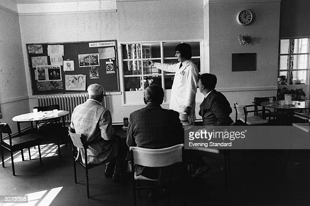 A doctor talking to three male patients in Runwell Psychiatric Hospital about Art Therapy