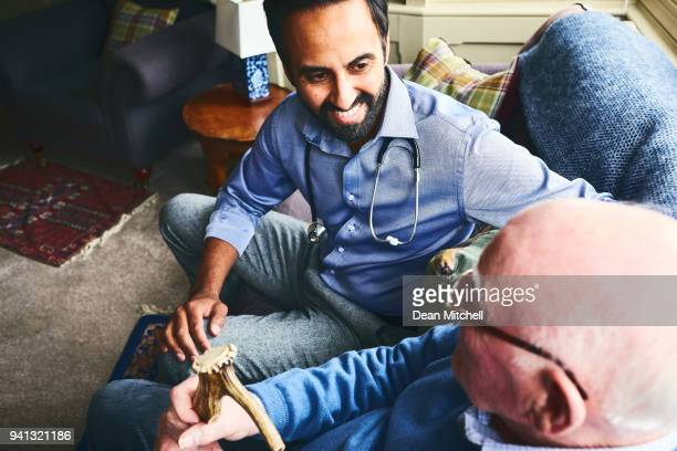 Doctor talking with elderly man in home visit