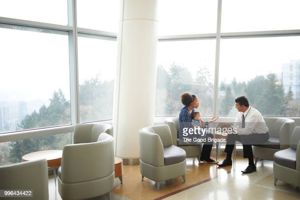 doctor talking with female patient in waiting room - patient room stock photos and pictures