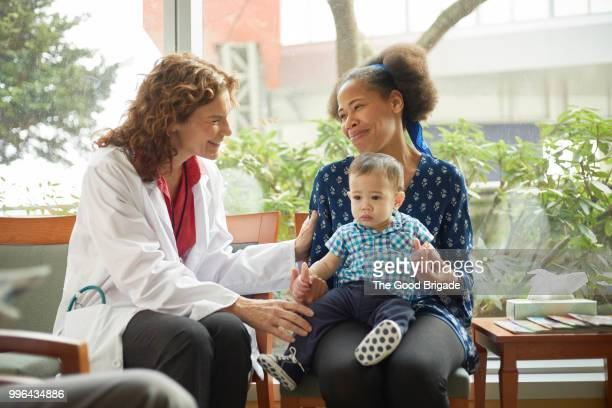 doctor talking with mother and baby in waiting room - family and happiness and diverse stock photos and pictures