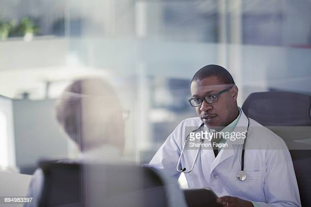 doctor talking with patient at desk in office - selective focus photos et images de collection