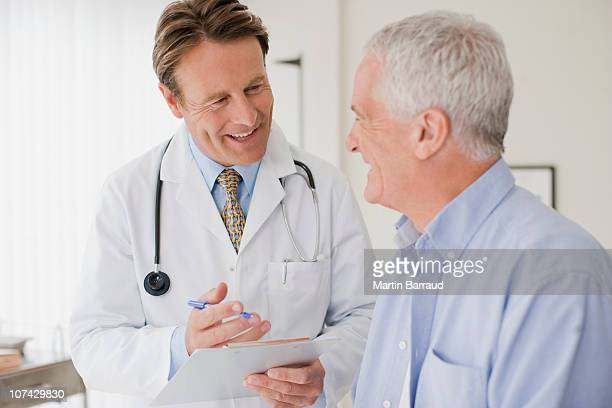 doctor talking with patient in doctors office - dokter stockfoto's en -beelden