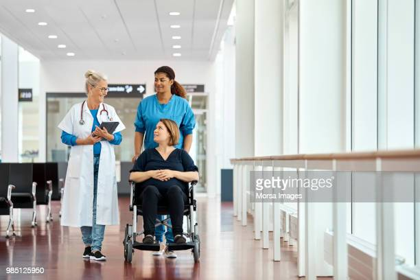 doctor talking with pregnant woman on wheelchair - wheelchair stock pictures, royalty-free photos & images