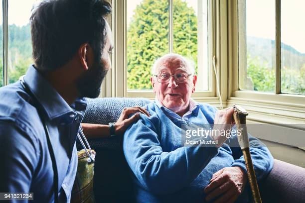 doctor talking with senior man in home visit - social services stock photos and pictures