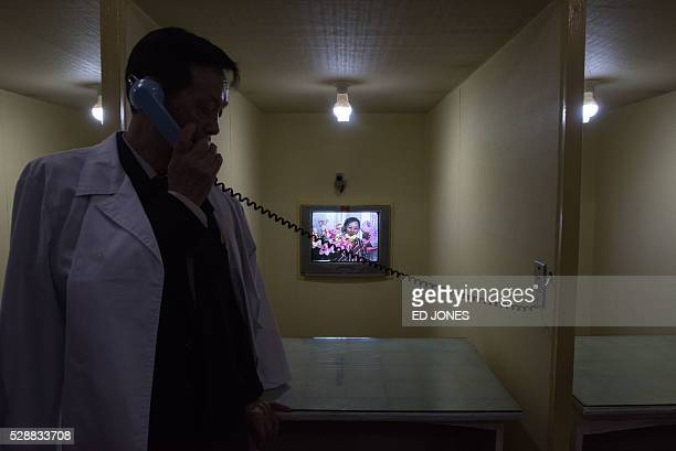 A doctor talks to a new mother holding her baby as she talks via telephone on a screen to journalists at the Pyongyang Maternity Hospital during a...
