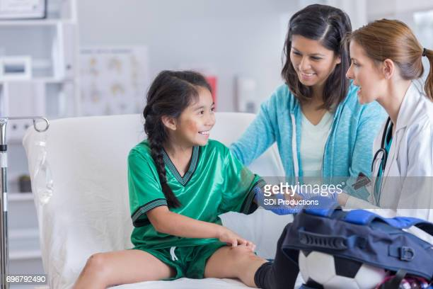 er doctor talks with injured soccer player - brace stock pictures, royalty-free photos & images