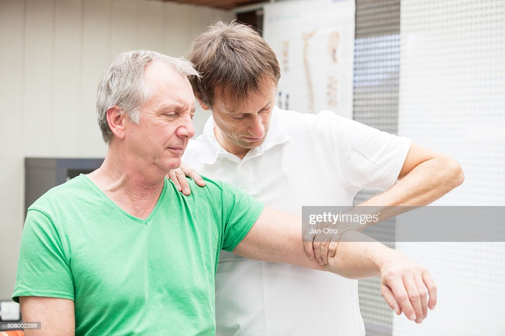 Doctor testing mobility of a patient`s shoulder : Stock Photo