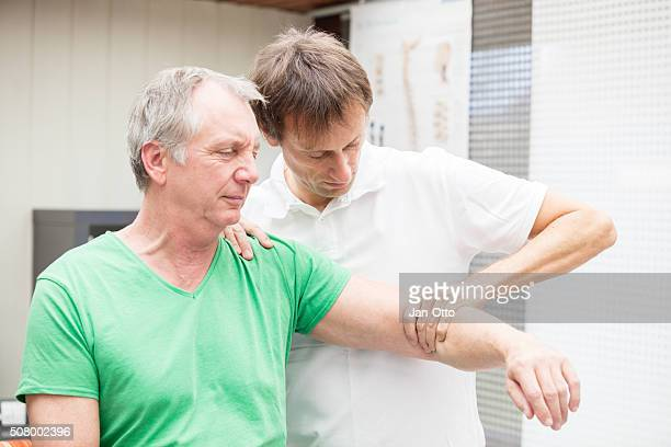 doctor testing mobility of a patient`s shoulder - osteoarthritis stock photos and pictures