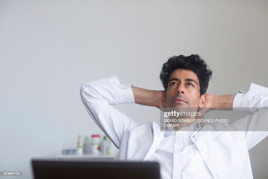 Doctor thinking at his desk : Stock-Foto