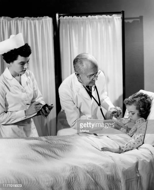 Doctor treat a little girl 19501960