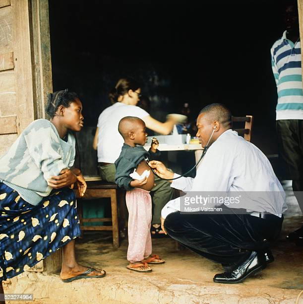 doctor treating boy in ghana - humanitarian aid stock pictures, royalty-free photos & images
