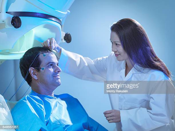 doctor treating patient using magnetoencephalography (meg) scanner - neuroscience stock pictures, royalty-free photos & images