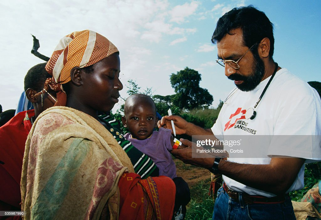 A doctor treats a young child being held by its mother at a Medecins Sans Frontieres refugee camp for Hutu and Tutsi refugees near Lake Cohoha in northern Burundi. The camp was created for refugees entering the country from Rwanda due to the inter-ethnic civil war. In April 1994, civil conflict broke out in Rwanda between Hutus and Tutsis, the two major ethnic groups in Burundi and Zaire, leading to widespread genocide in Rwanda. During the war, approximately 63,000 refugees (mainly Tutsi) poured into northern Burundi.