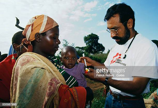 A doctor treats a young child being held by its mother at a Medecins Sans Frontieres refugee camp for Hutu and Tutsi refugees near Lake Cohoha in...