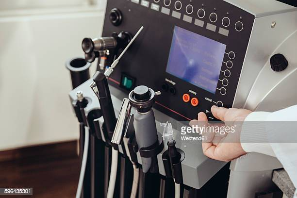 ENT doctor turning a knob at medical device in practice