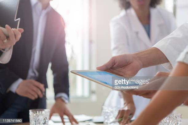 doctor uses tablet during meeting - sales occupation stock pictures, royalty-free photos & images