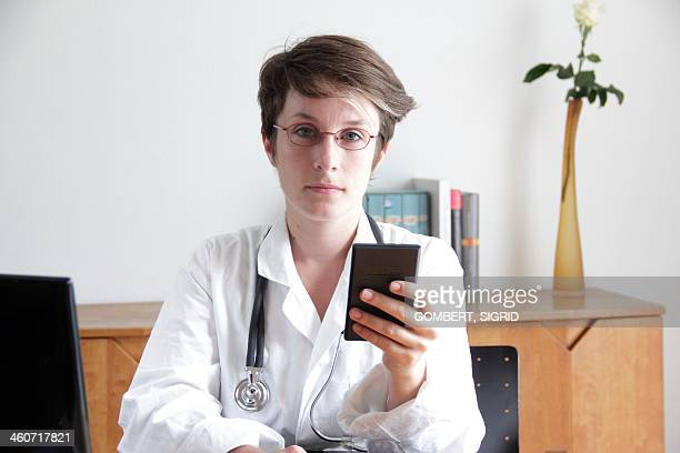 doctor using a mobile phone - sigrid gombert stock pictures, royalty-free photos & images