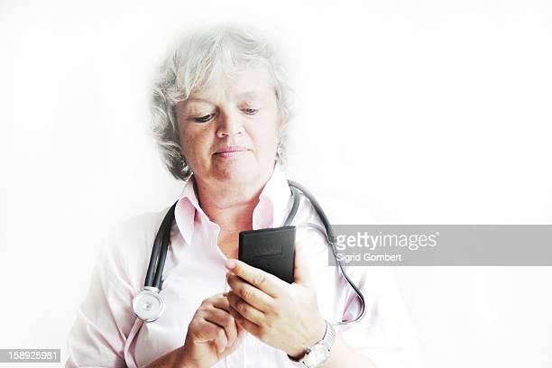 doctor using calculator in office - sigrid gombert fotografías e imágenes de stock