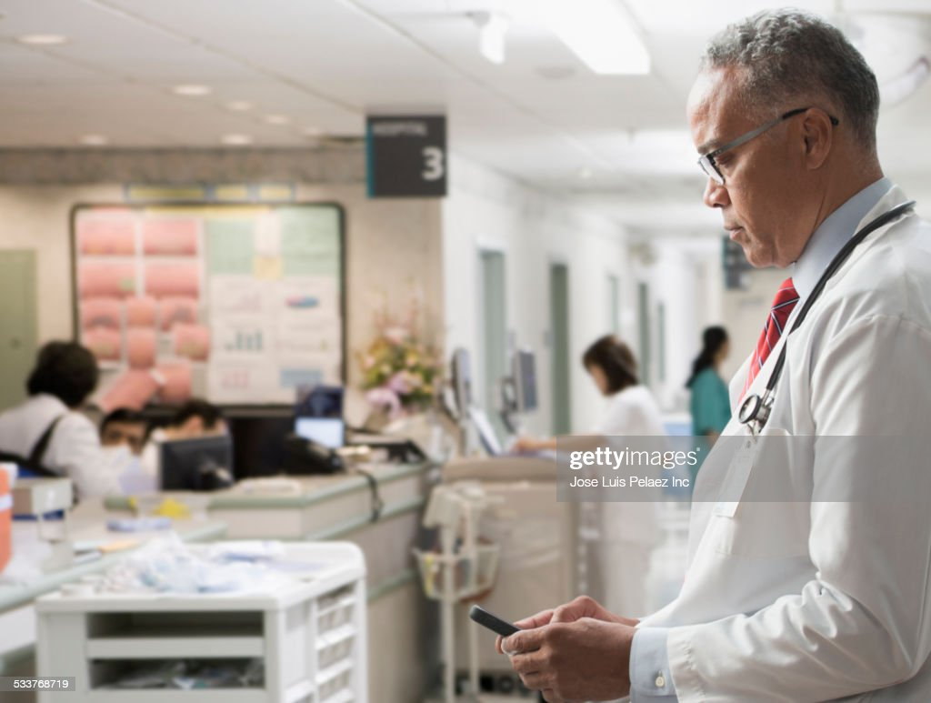 Doctor using cell phone in hospital : Foto stock