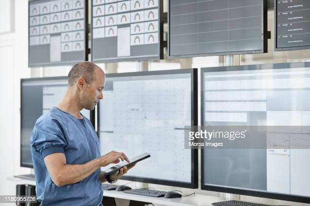 doctor using digital tablet in control room - computer equipment stock pictures, royalty-free photos & images
