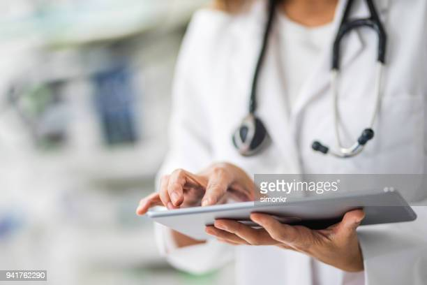 doctor using digital tablet - doctor stock pictures, royalty-free photos & images