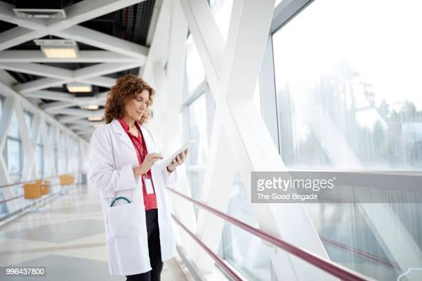 doctor using digital tablet while standing in hospital corridor - saúde e medicina - fotografias e filmes do acervo