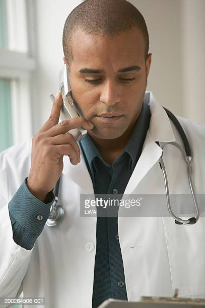 doctor using mobile phone - part of a series stock pictures, royalty-free photos & images