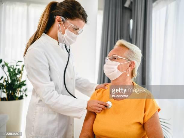 medico che usa stetoscopio ascoltando i pazienti anziani che respirano - cardiologo foto e immagini stock