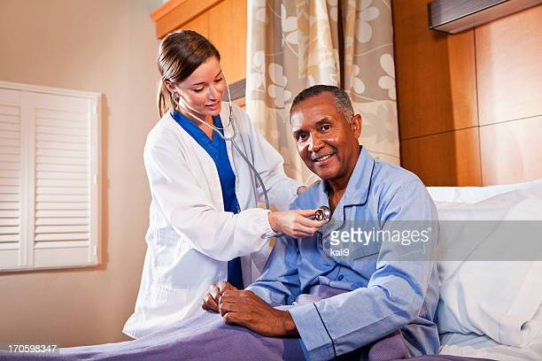 Doctor using stethoscope on senior patient