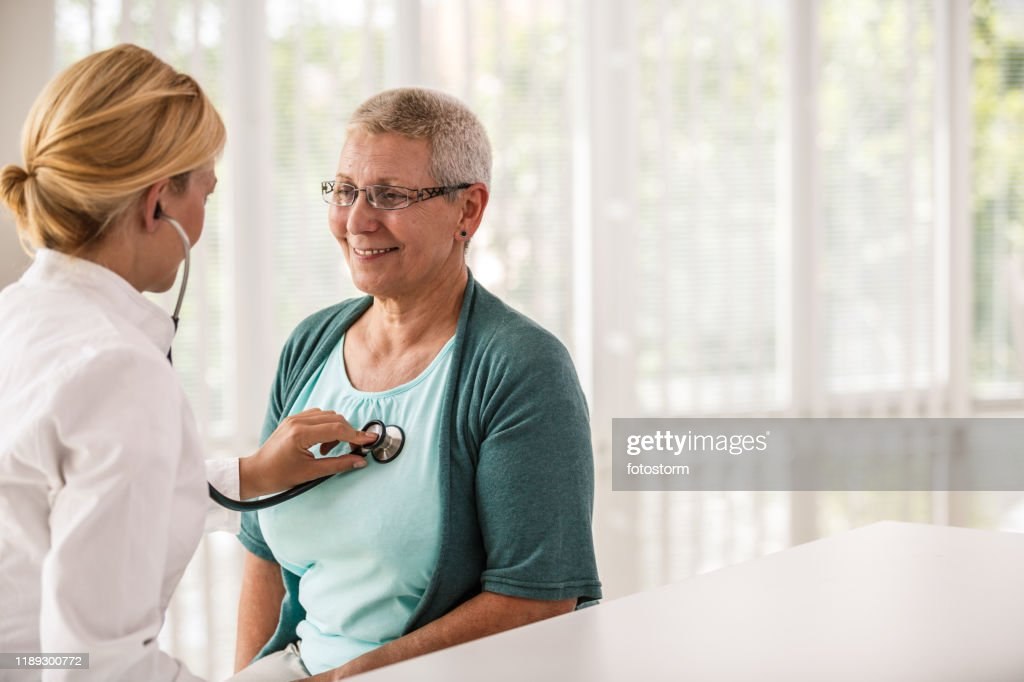 Doctor using stethoscope while examining patient : Stock Photo